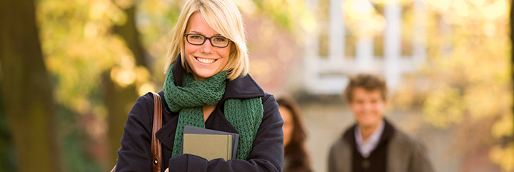 Young woman carrying books with older adults in background