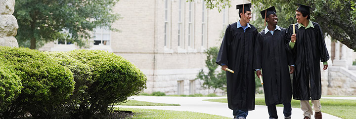Three young men in graduation robes walking on college campus