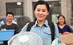 Young woman and older adults carrying items