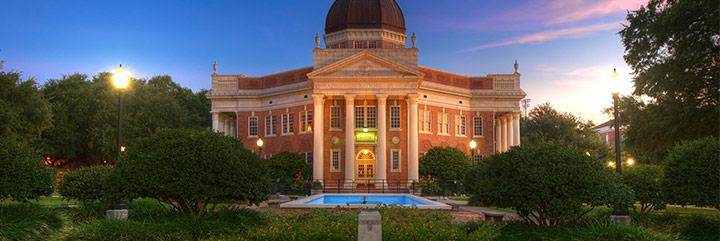 Neo-classical domed building in campus setting at twilight