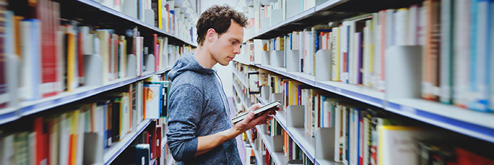 Young man in stacks at library looking at a book