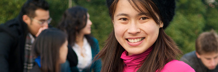 Young Asian woman outdoors with other young people in background