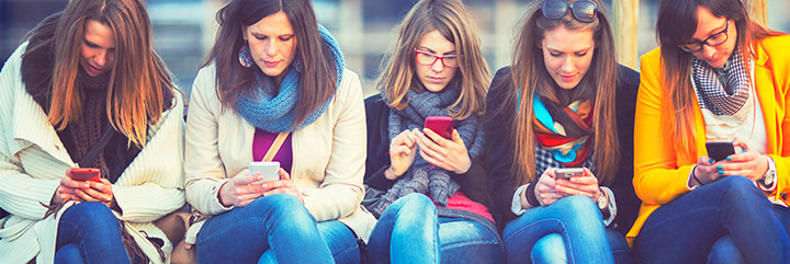 Row of young women on bench all looking at their smart phones