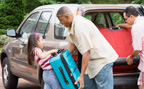 Two men and young girl behind station wagon move luggage